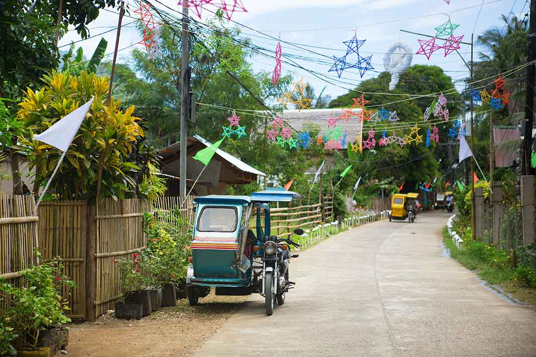 A Philippino village with decorations hanging overhead and traditional motorbike with covered sidecar parked on the side of the road