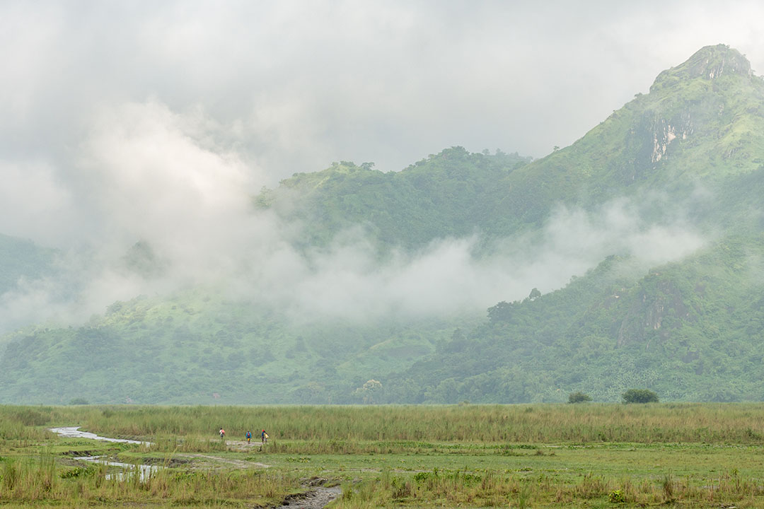 Mist hangs low over green mountains and flat wetlands