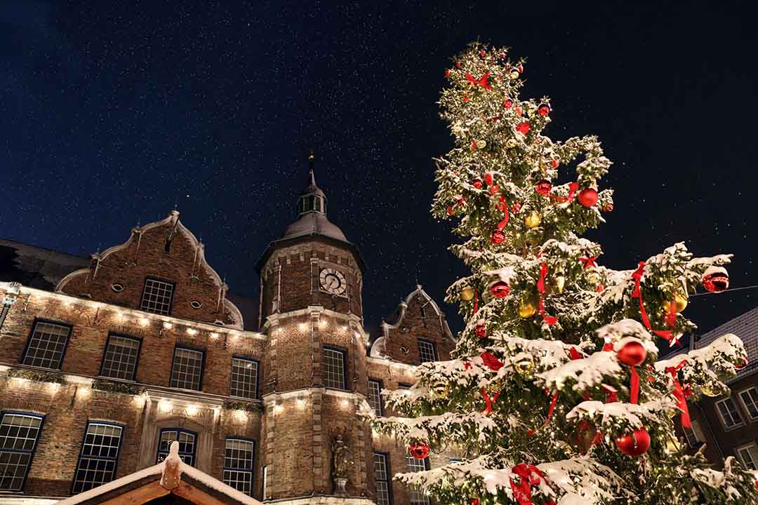 A snowcapped Christmas tree in the foreground with a stone building with clocktower in the background.. Snowflakes can be seen in the night sky.