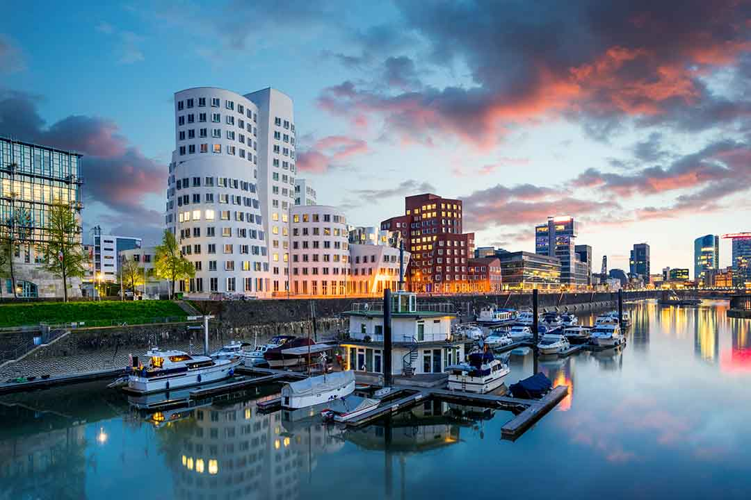 Medienhafen and marina area of the city of Düsseldorf. Ships are moored at the rivers edge and tall angular modern buildings line the shore