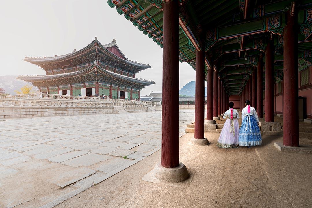 Asian Korean woman dressed Hanbok in traditional dress walking in Gyeongbokgung Palace.