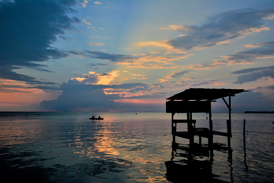 Sunset across a still, blue lake