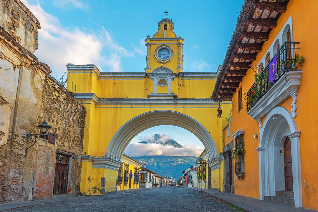 The famous architecture and yellow arch in the main street of Antigua at sunrise with the active Agua volcano in the background, Guatemala.