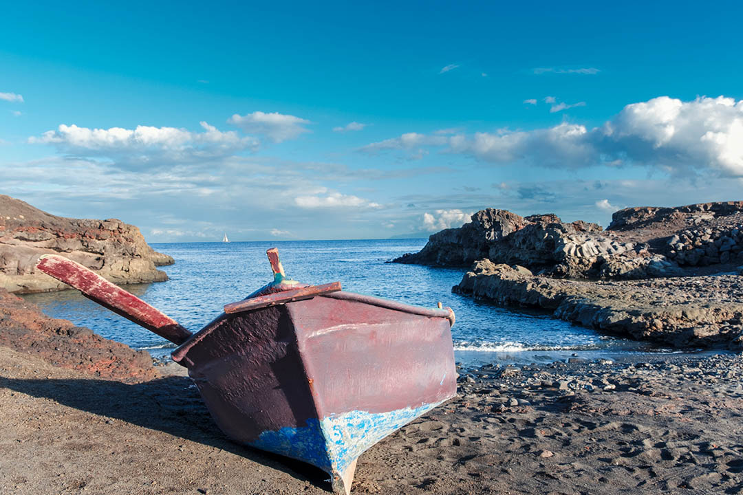 A wooden boat moored in sand