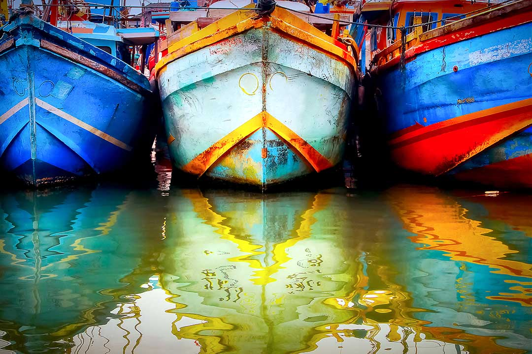 Multicolored old boat in the fishing port. Colored reflections in the water.