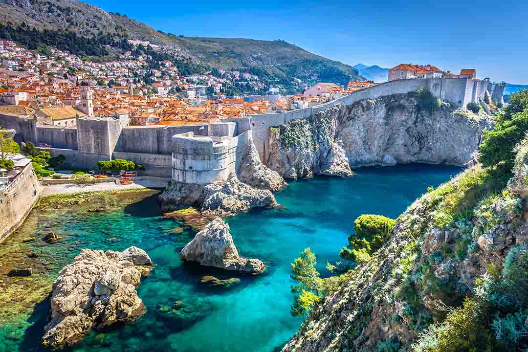 A landscape of Dubrovnik with bright blue waters and a towering wall around the town