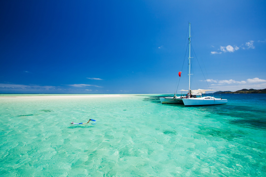 A catamaran sits atop still and tranquil blue waters