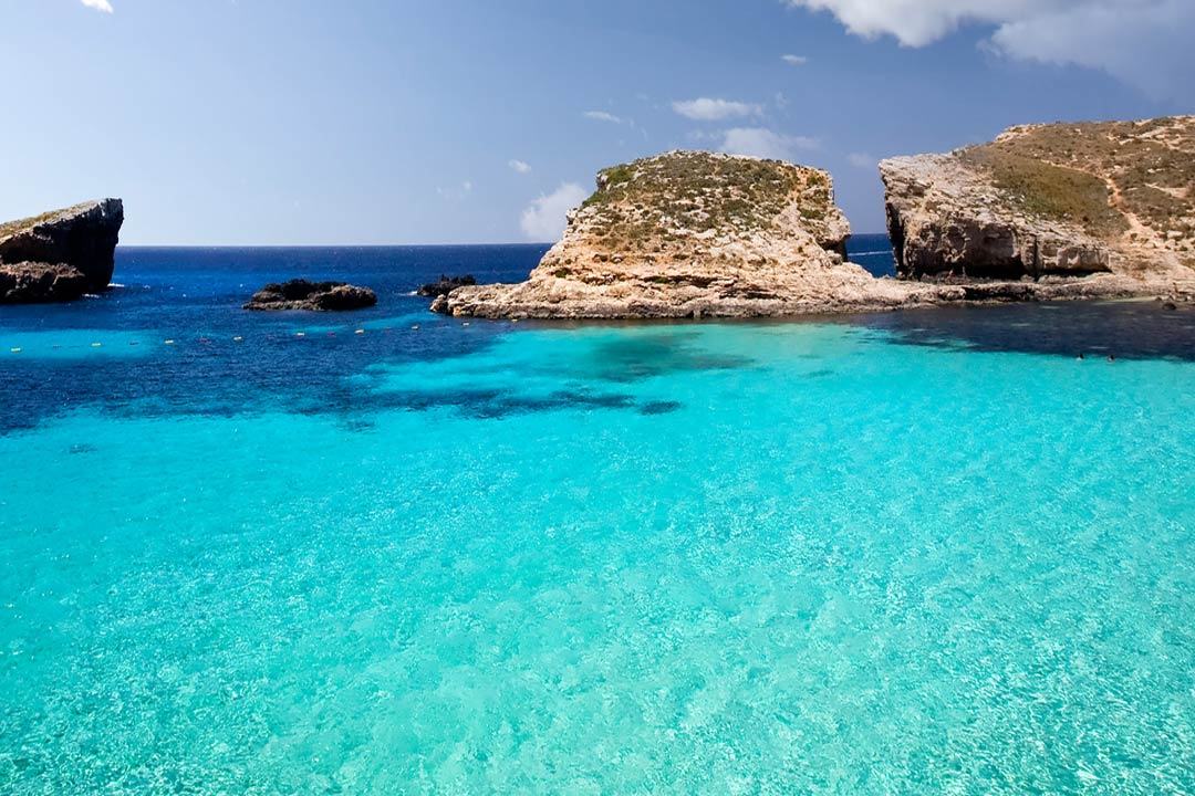 Crystal clear blue waters and a small piece of rocky land