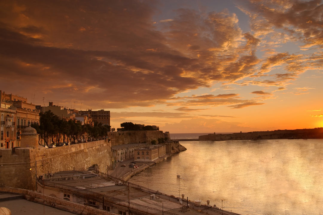 The edge of Valletta meeting the water at sunset