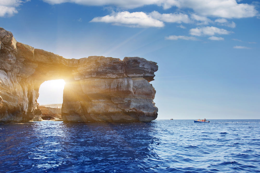 Azure window with sun peaking through and dazzling blue waters