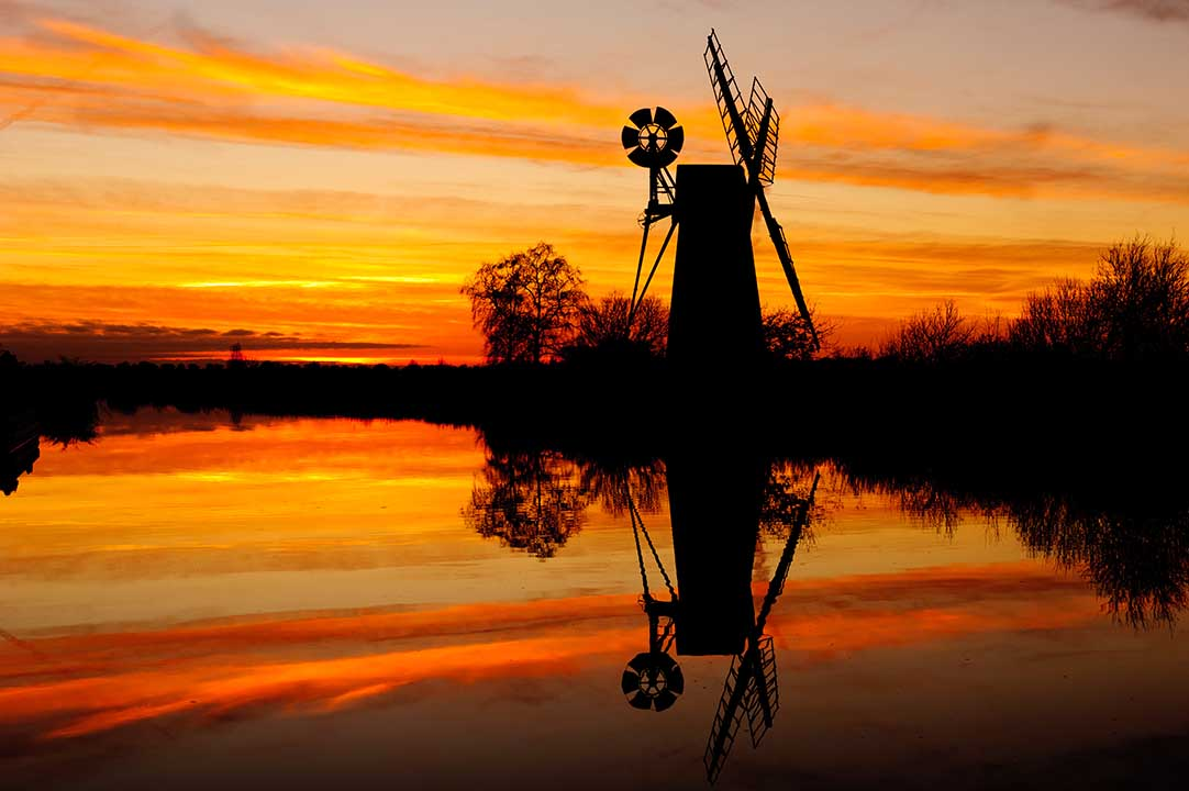 Sunset silhouette at How Hill, Ludham in Norfolk England. A traditional wind pump.