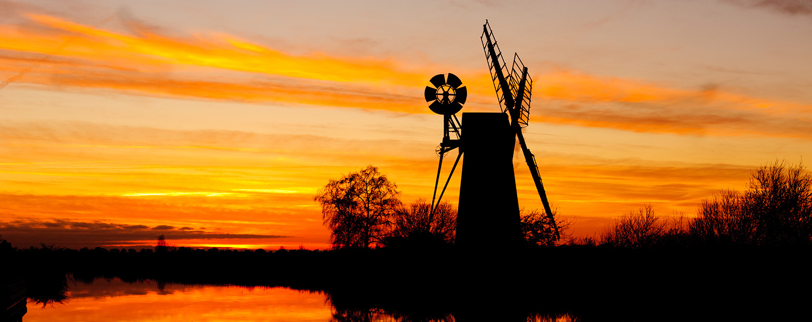 Sunset silhouette at How Hill, Ludham in Norfolk England. A traditional