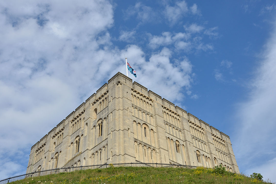 Looking up at Norwich Castle on green hill with blue sky in background