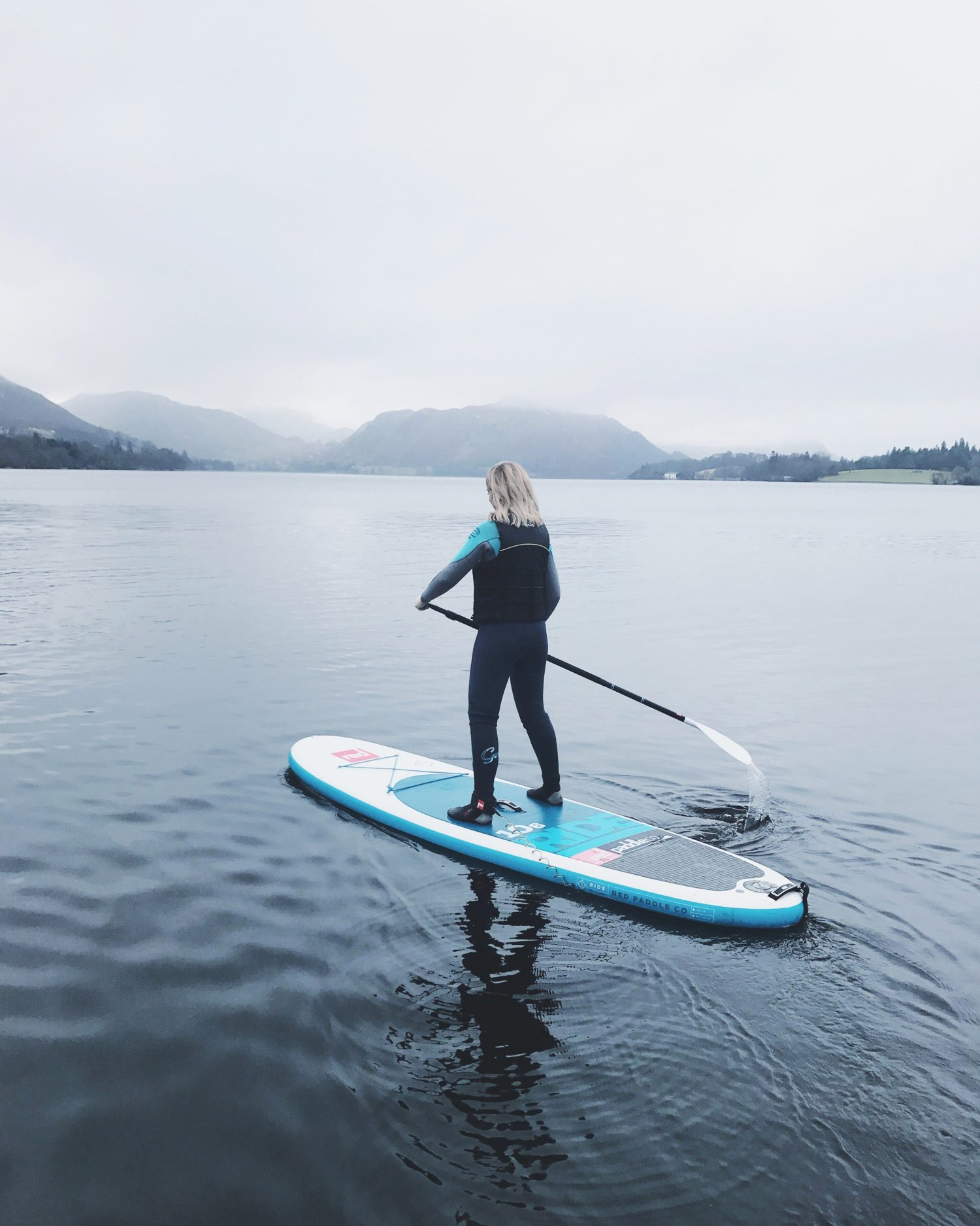 Emma on a stand up paddle board on a vast lake with mountains shrouded in cloud