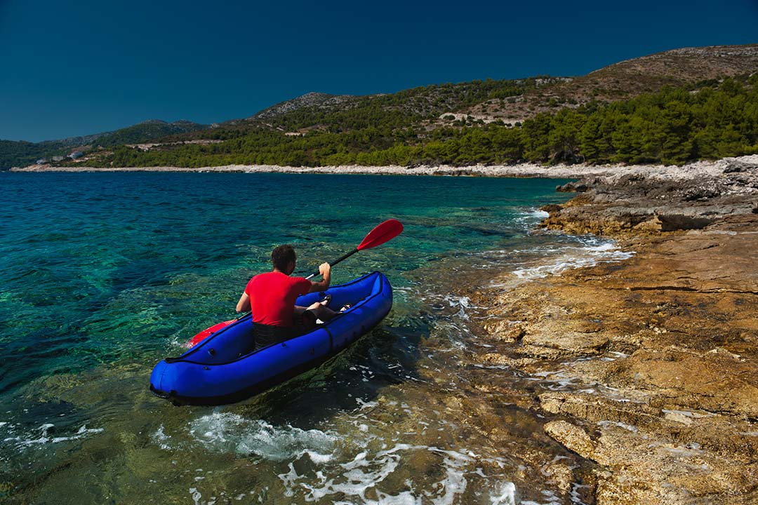 A man kayaking around a bay with crystal clear waters