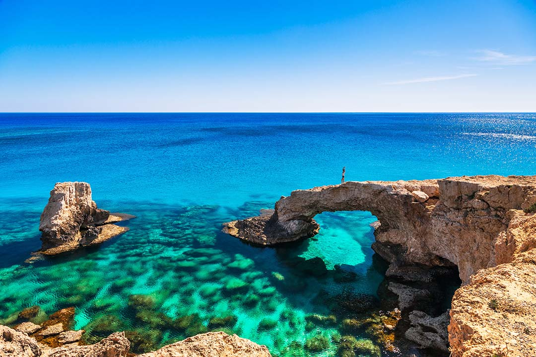 A lone woman atop a beautiful natural rock arch surrounded by bright blue waters