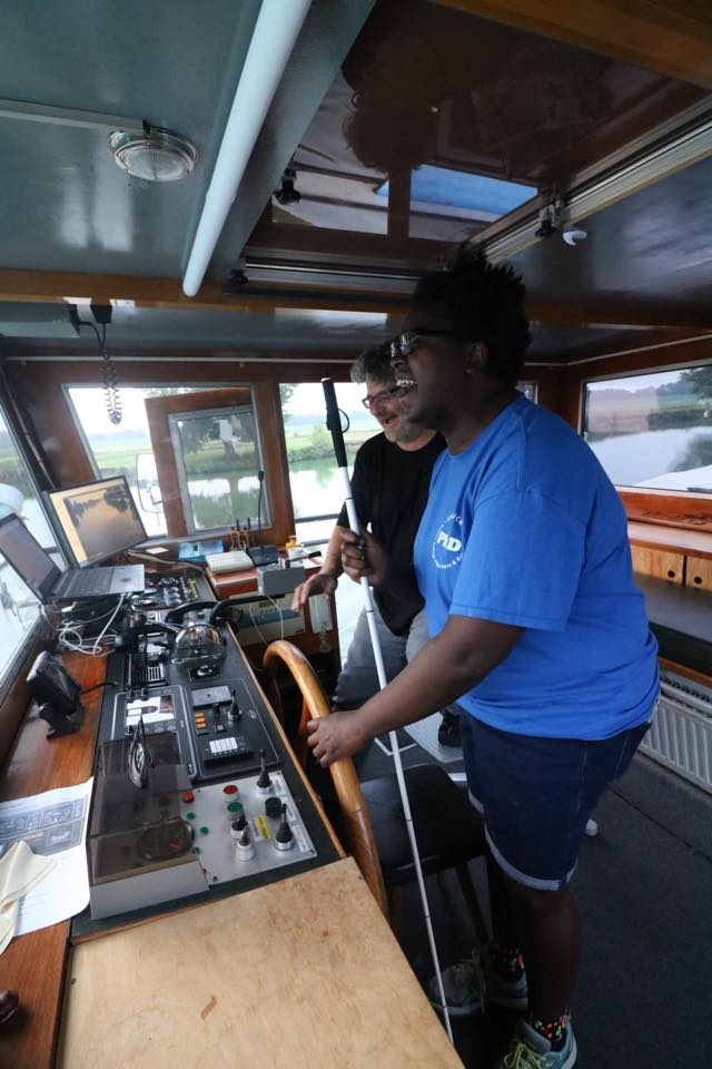 image of Denna and the captain of the barge, Ivo in the bridge, Denna is steering the barge and both are laughing.