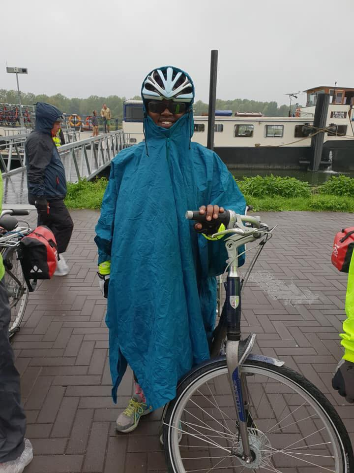 image of Denna in a rain coat stood by her bike with the barge in the background.