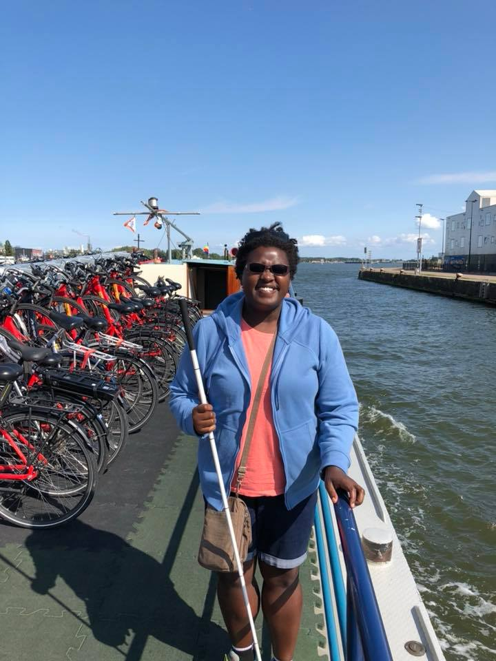 Image of Denna on the barge with clear blue skies and rows of red bikes