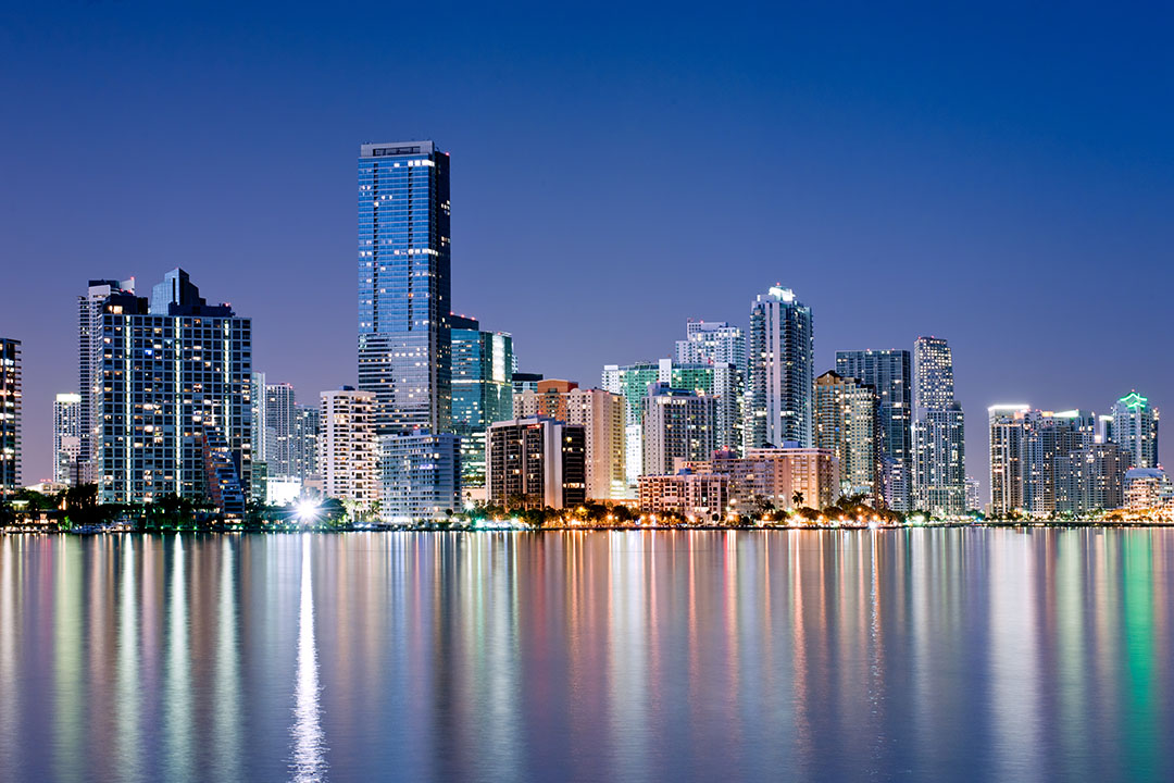 shimmering skyline of Miami along Biscayne bay on cloudless night