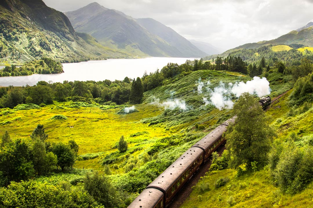 An old steam train rambling through the breath taking green countryside
