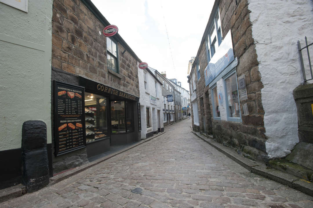 A cobbled street in St Ives with shops and Cornish pasty bakery on either side