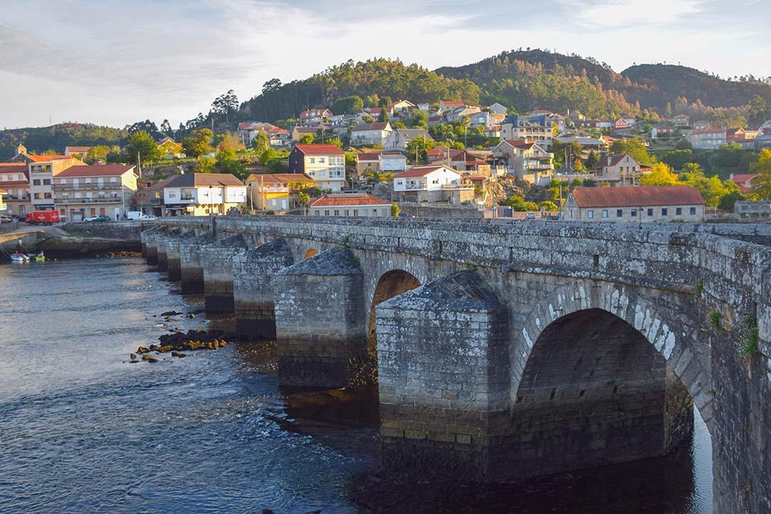An old stone bridge over gentle waters
