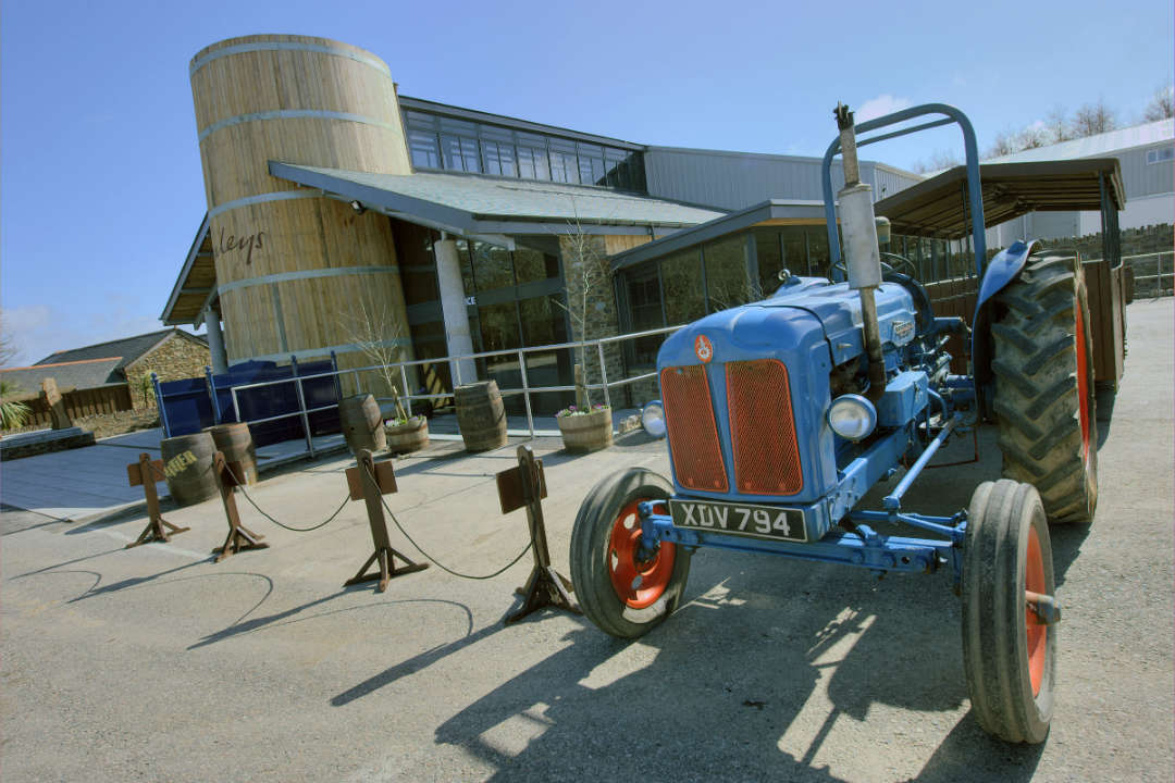 A blue tractor outside the entrance to Healeys Cornish Cyder Farm