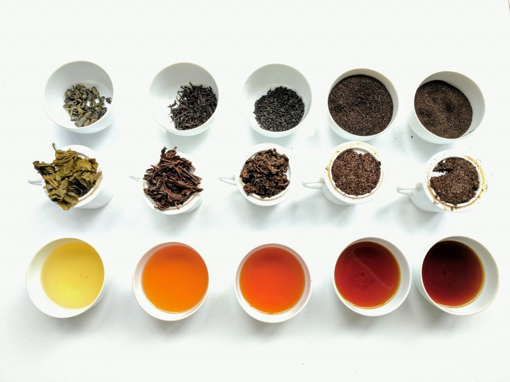 Image of the different colours of tea found in Sri Lanka. There are three rows of cups, at the top with dried leaves, the middles with full leaves and the bottom is the colour of the water.
