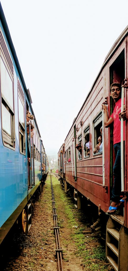 A photo of two train stopped side by side, both old looking trains, the left one is blue the right is red and you can see people stood and sat in the door ways of each carriage.