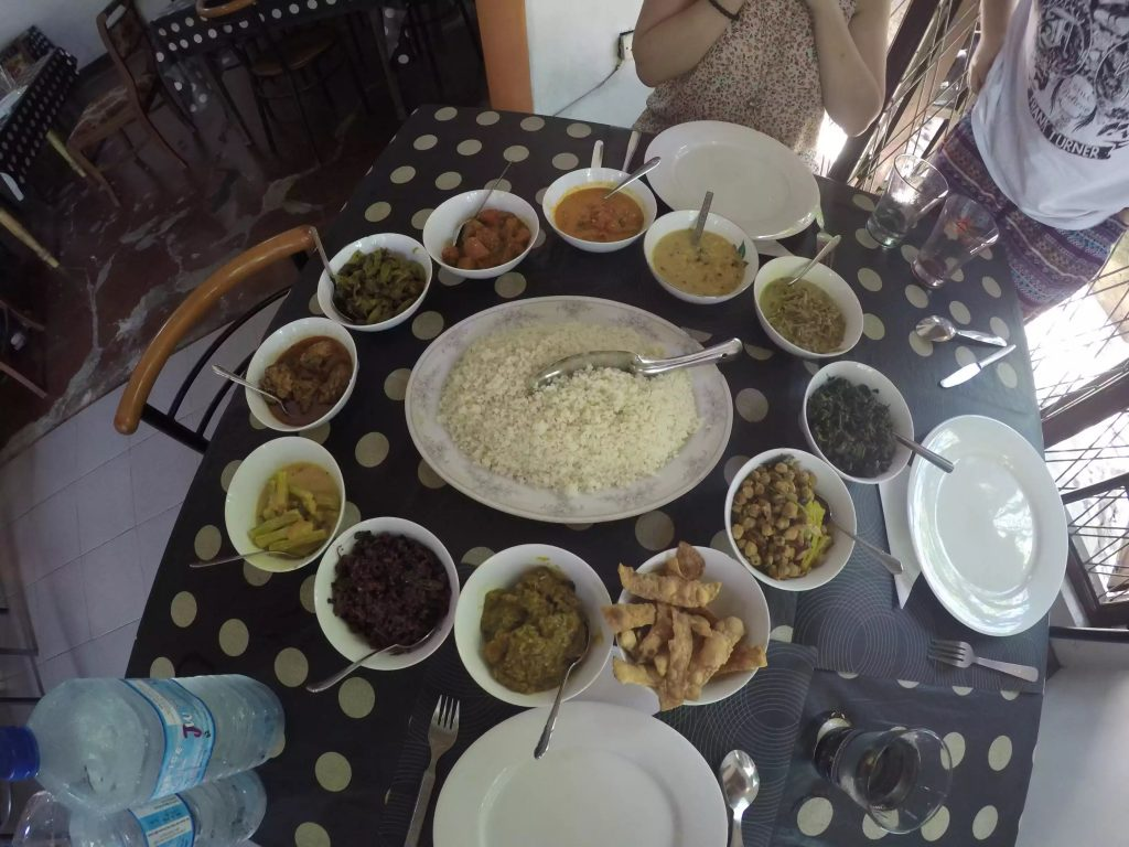 An image of a tradition Sri Lankan meal. A big bowl of rice in the middle and then 12 different dishes surrounding the rice. All variant spice levels, colours and flavours.