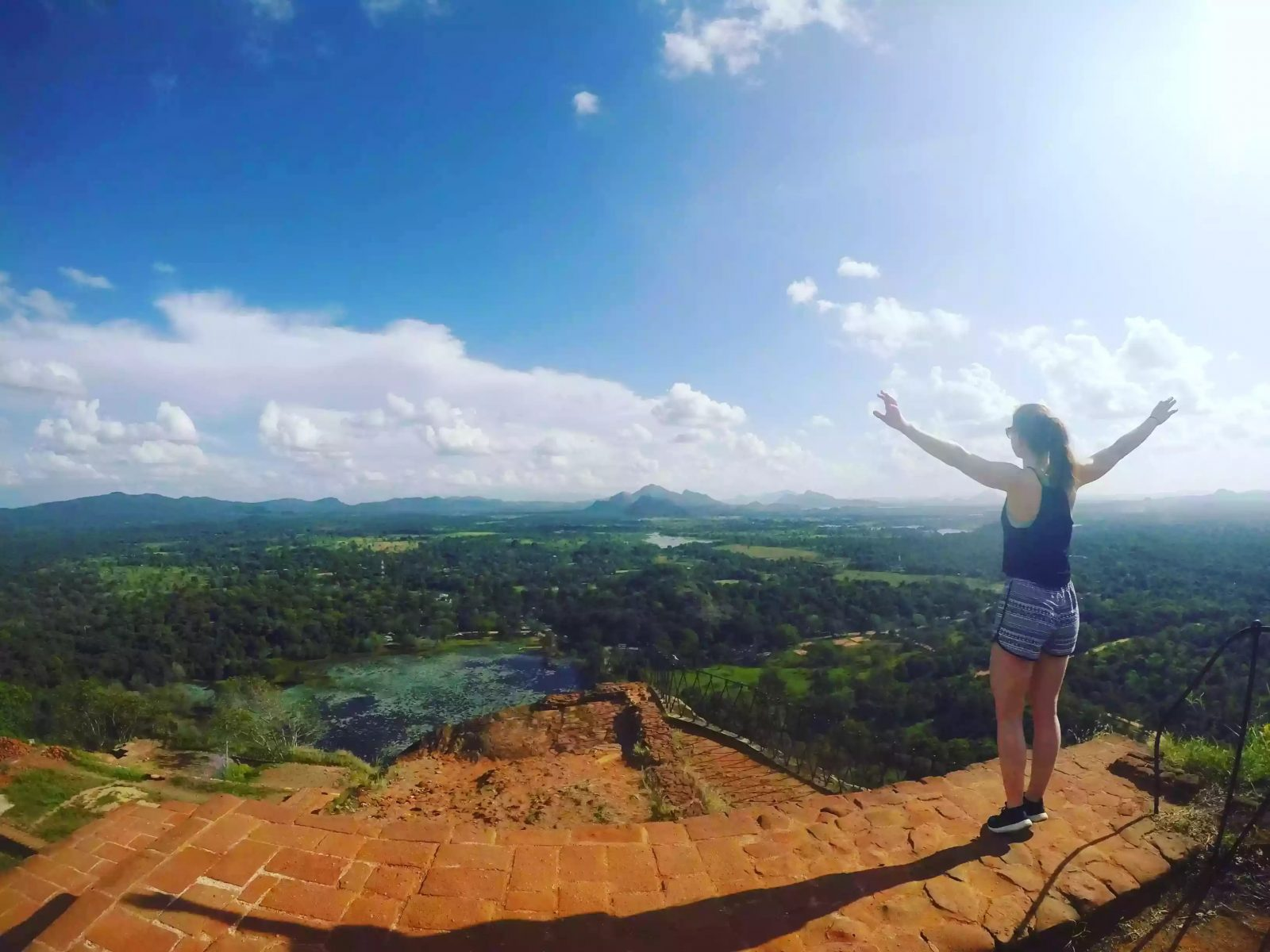 Image of Laura stood at the top of Sigiriya Rock, overlooking a lush green landscape with bright blue skies.