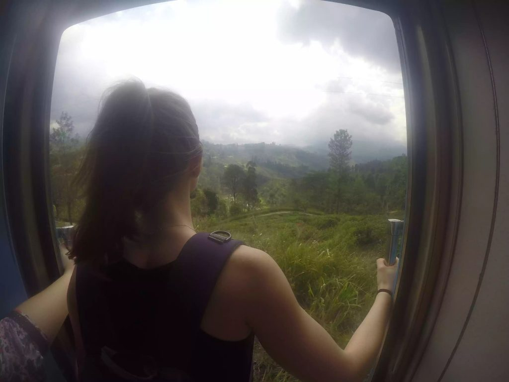 Image of Laura stood in the doorway of the train heading from Kandy to Ella. Laura is looking out over the lush green countryside.