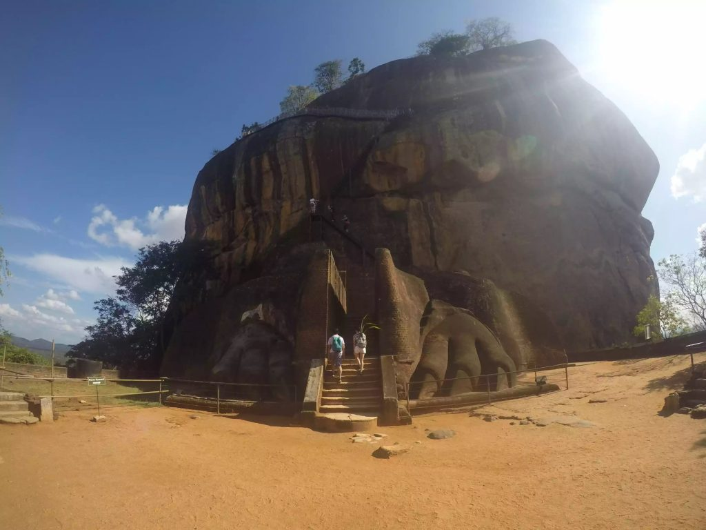 Image of the base of Sigiriya Rock. The rock has lions feet caved into it and the stairs go between the feet.