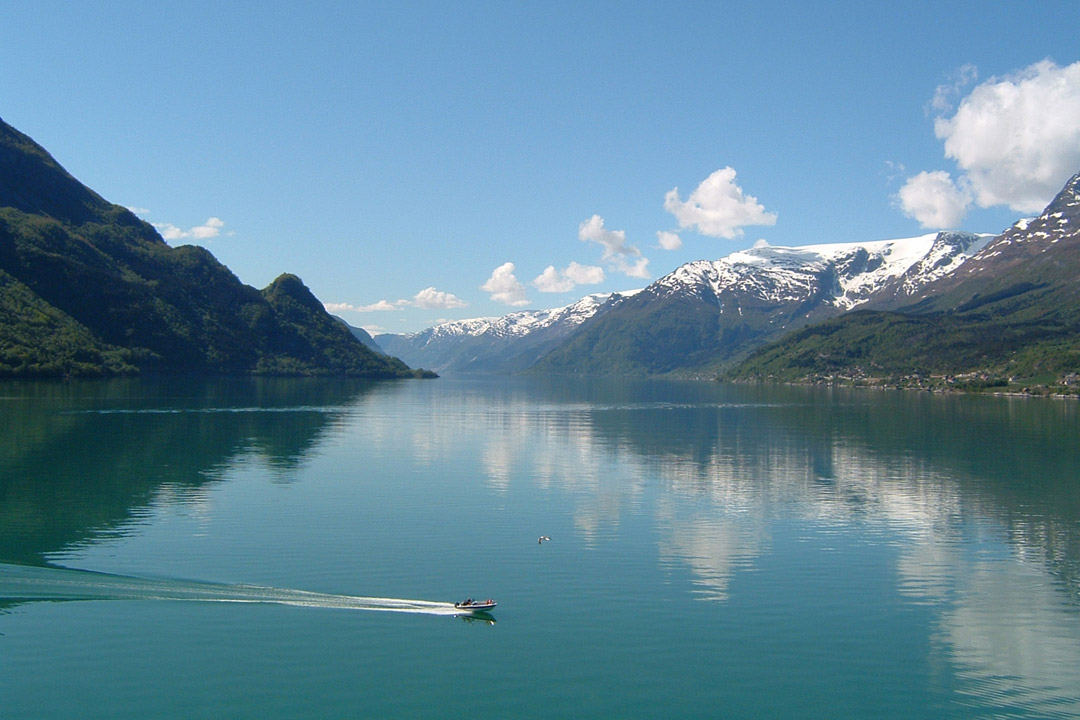 A landscape view down a Norwegian fjord with mountains on either side and blue water and a sailing boat in the middle