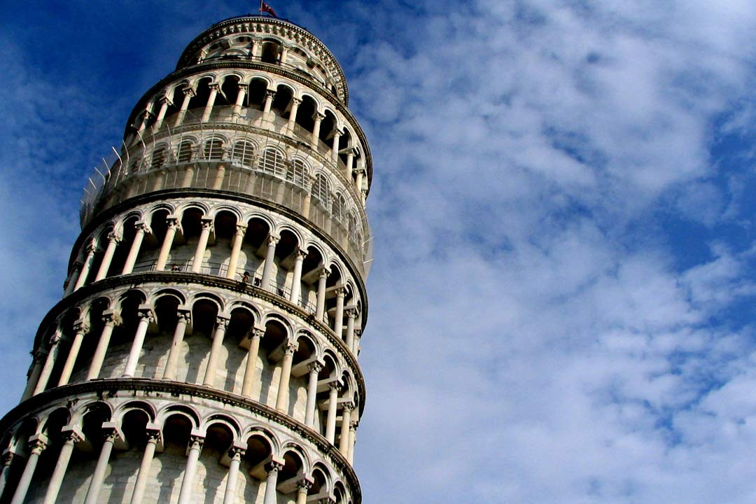 The top of the Leaning Tower of Pisa against a deep blue sky