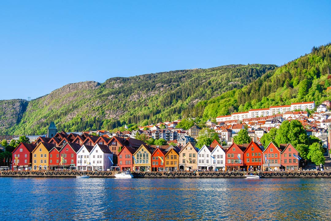 Red, white, blue, green and orange Norwegian houses on the edge of the water with green mountains behind.