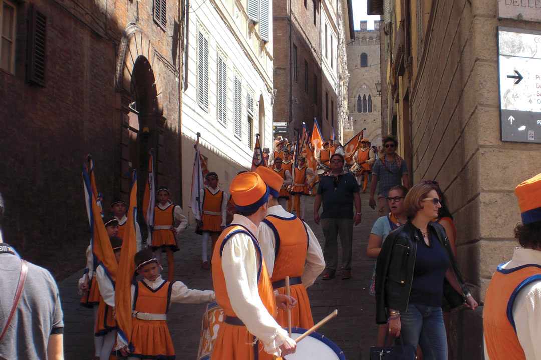 A troop of traditionally dressed Italian children march through a town with orange flags