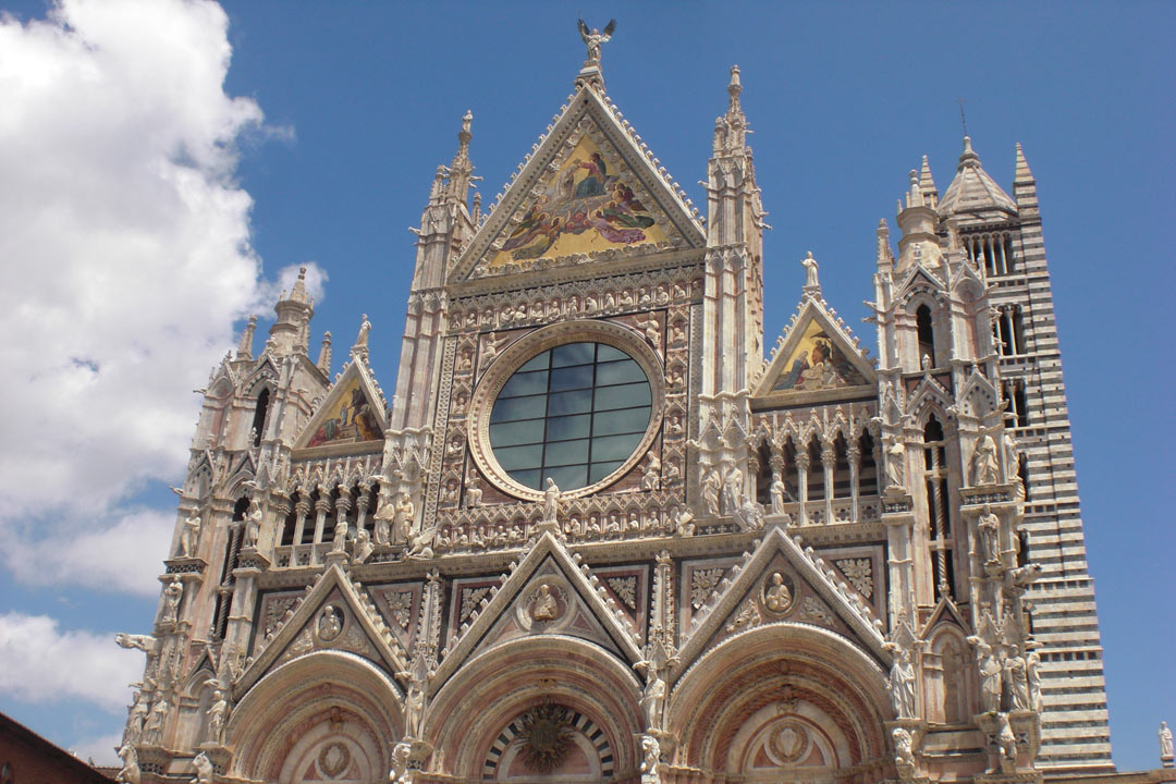 An ornately decorated basilica in Siena made of red, white and black marble