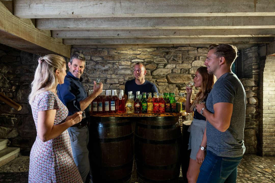 4 people stood around a bar tasting cyder at Healeys Cornish Cyder Farm