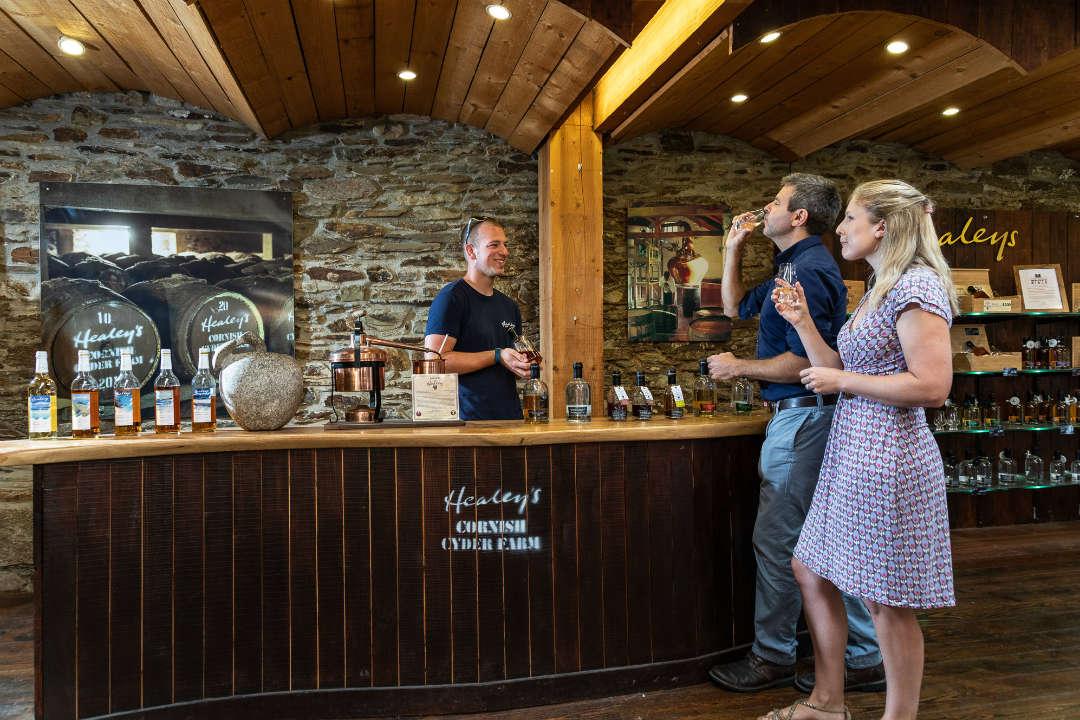 2 people stood at a bar tasting cyder