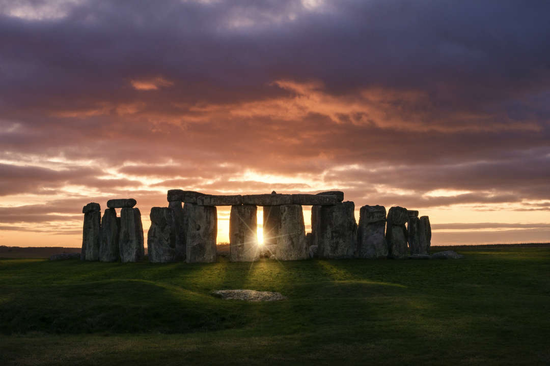 A landscape view of Stonehenge at sunset
