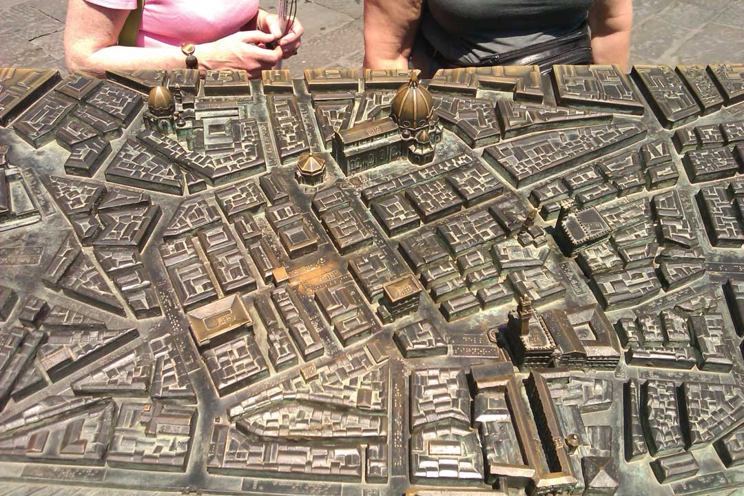 Traveleyes travellers next to a bronze tactile map of Florence