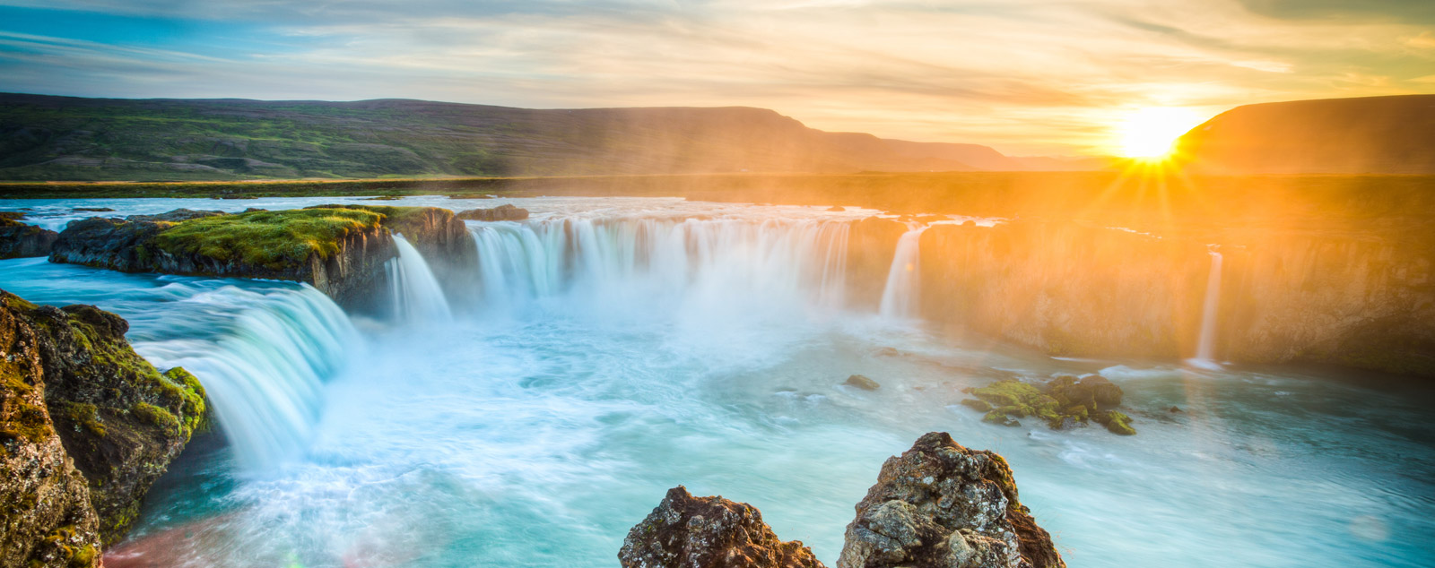 Banner of waterfall with setting sun behind
