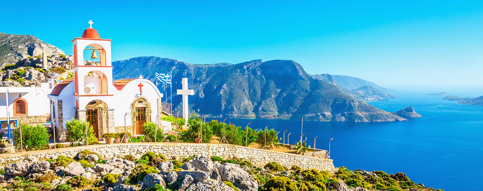 A beautiful white church perched atop a cliff, with turquoise waters in the background