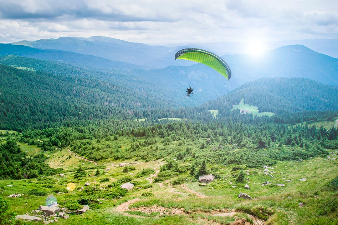 A single paraglider drifting over a stunning backdrop of a lush green valley
