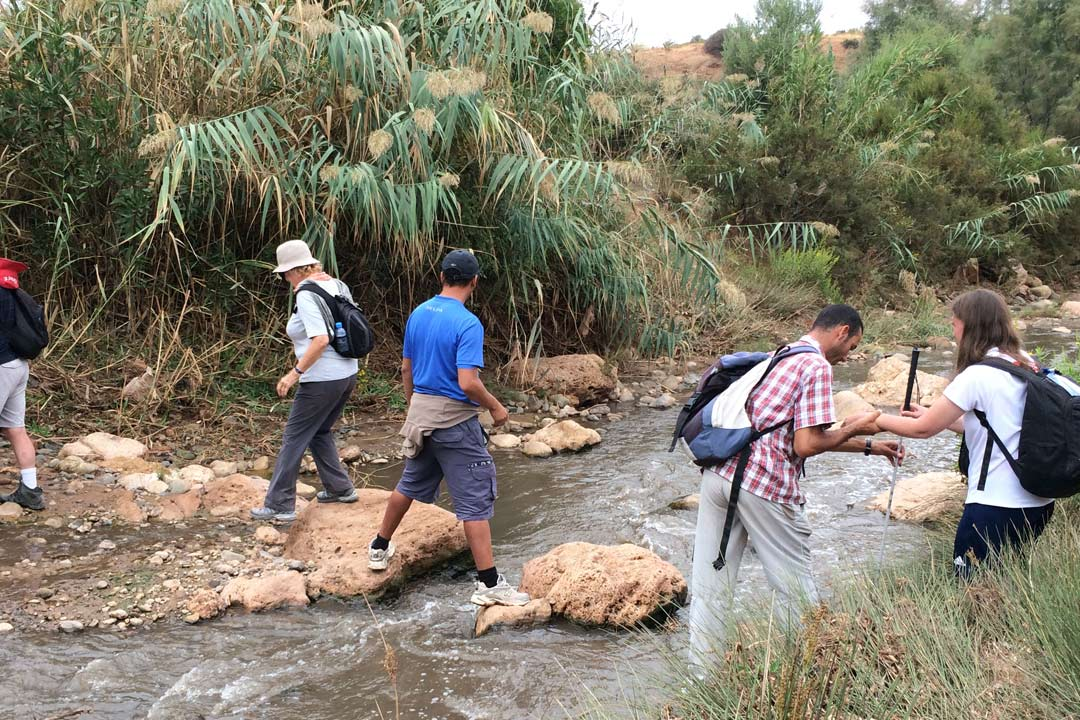 A group of Traveleyes travellers crossing a river on stepping stones