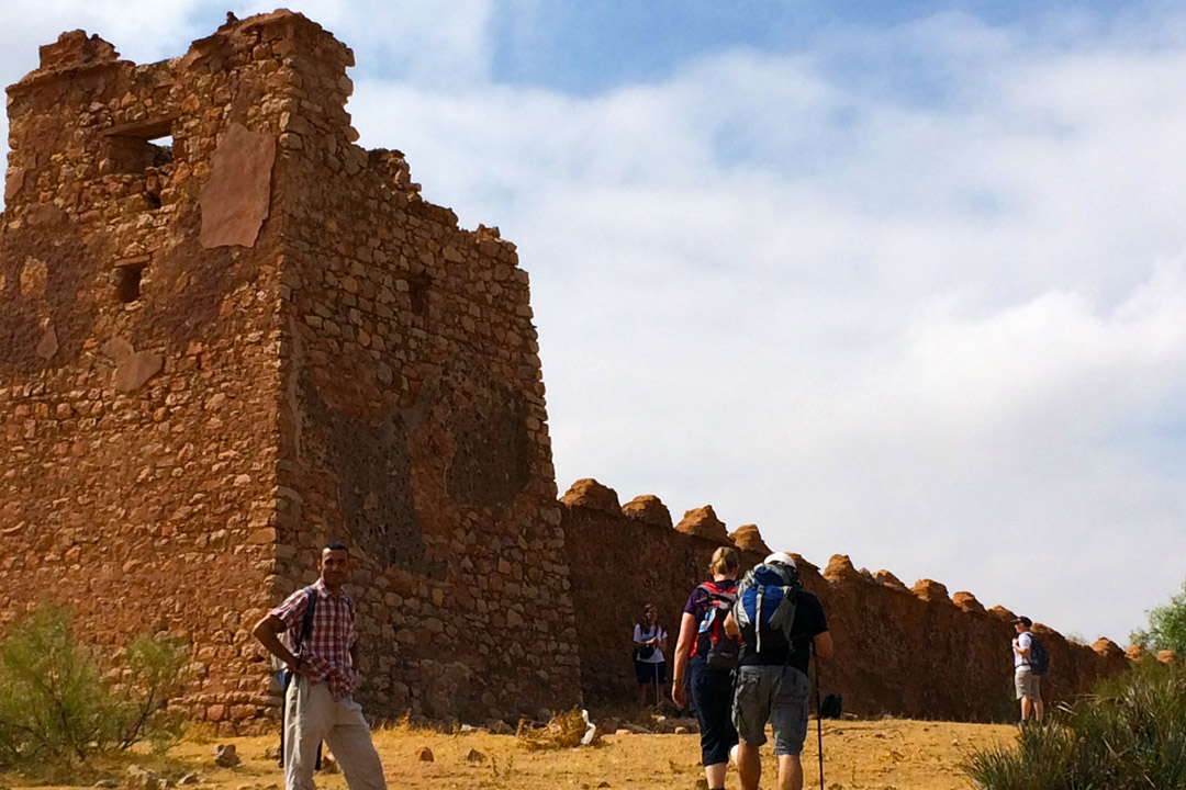 A Moroccan man stands next to a ruined French fort in the Atlas Mountains with hikers strolling by