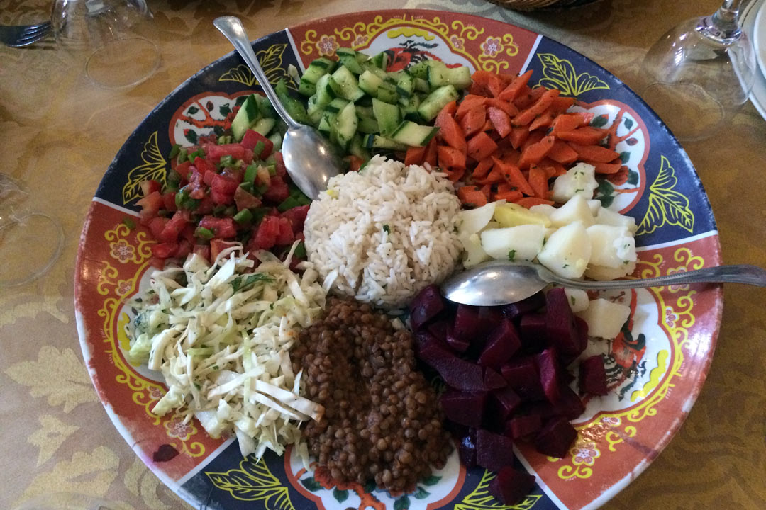 A dish composed of lentils, beetroot, potatoe salad, carrots, cucumber and coleslaw arranged in a circle