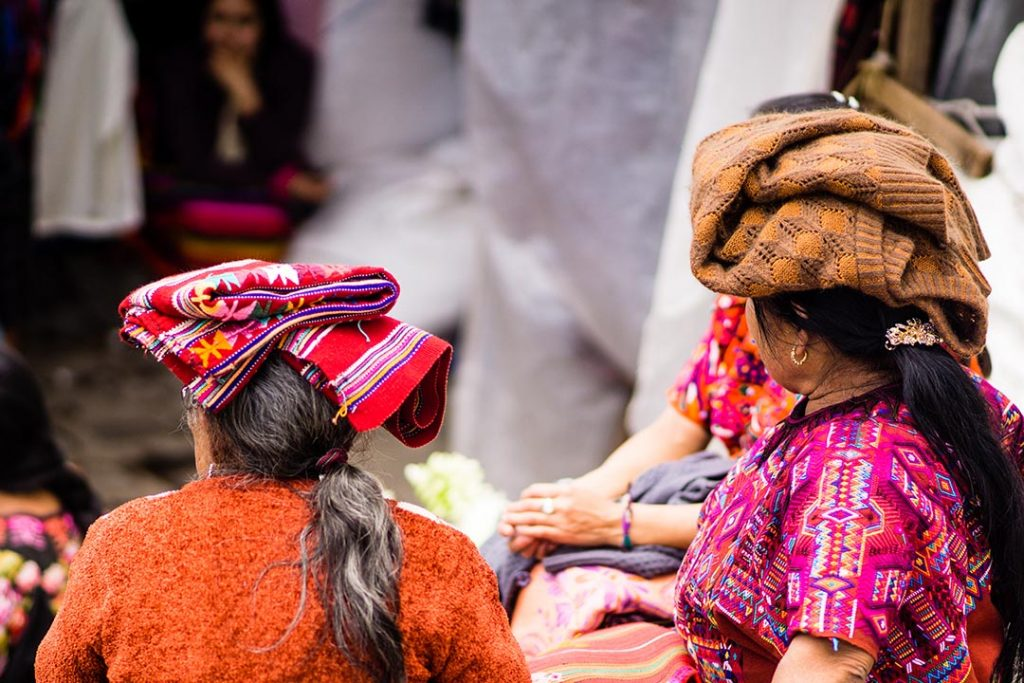 Two Guatemalan women balancing woven materials on their heads, dressed in vivid outfits.